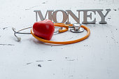 Closeup of money word and medical items with red heart