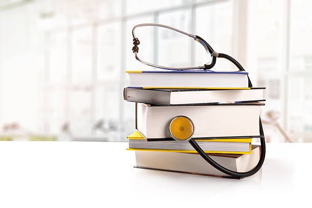 medical education - books on the table in library - literature stock pictures, royalty-free photos & images