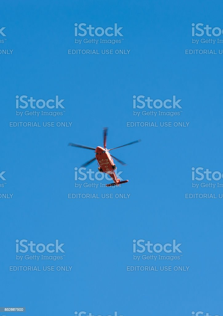 Medical emergency helicopter passes overhead on blue sky. stock photo