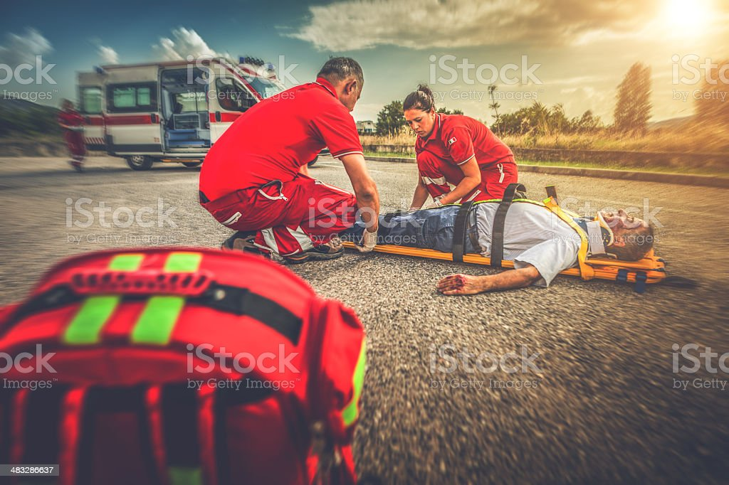 Medical emergency team soccurring man at street accident stock photo