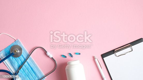 Medical equipment on pink background. Flat lay surgical mask, stethoscope, pills, medical clipboard and pen. Top view doctors table. Healthcare and medicine concept