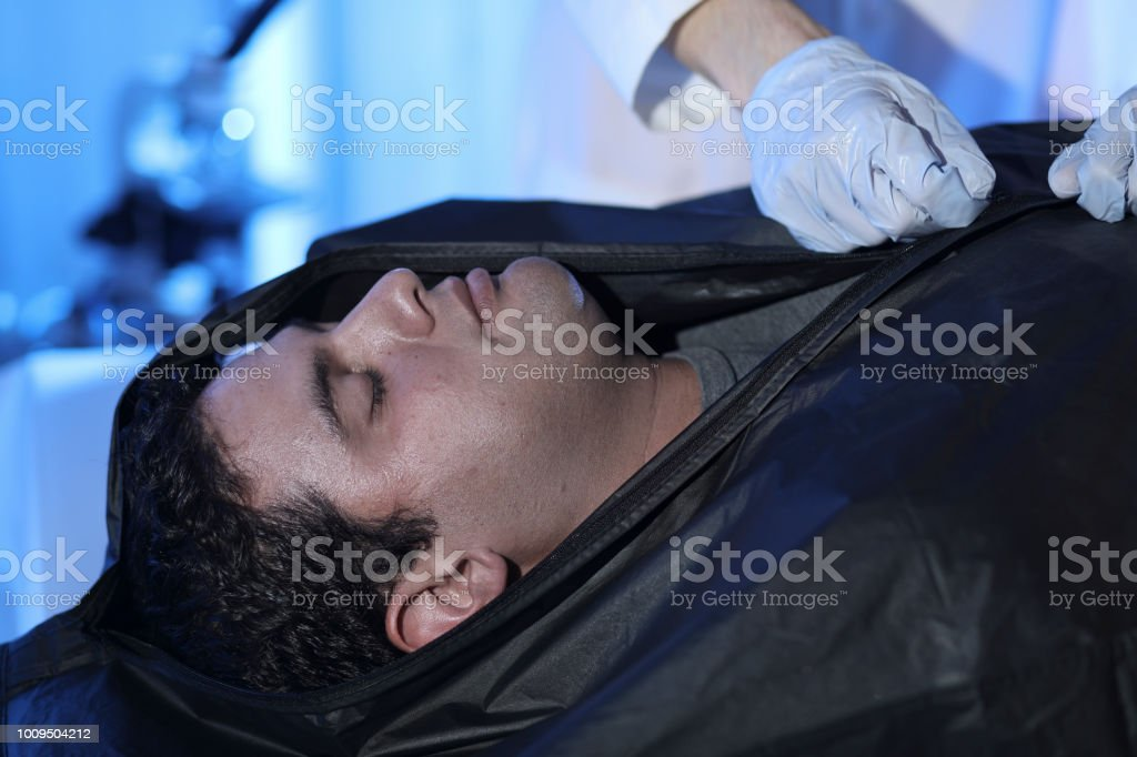 Medical Examiner with corpse in morgue. stock photo