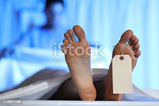 Medical examiner or forensic scientist with dead man's corpse in morgue.  He covers up the deceased man's body with a white sheet after autopsy.  Toes and toe tag focus.