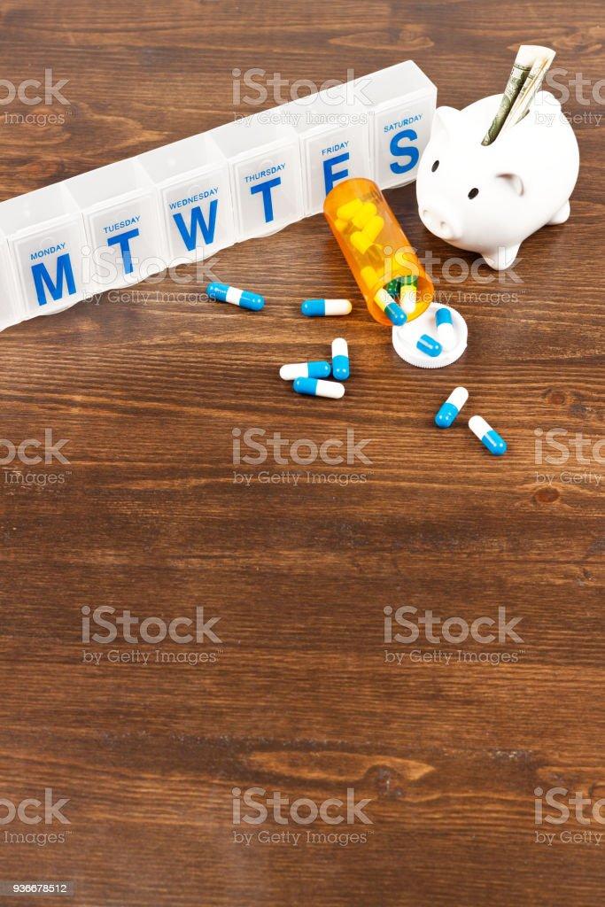 selection of medical supplies, dosette box, pills and savings bank