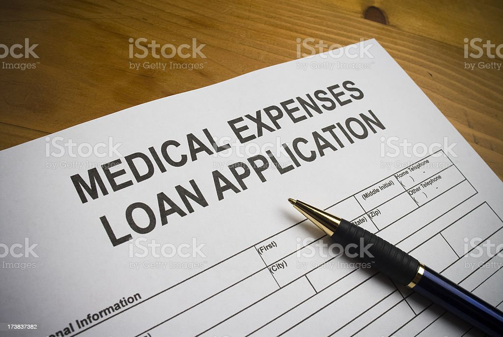 Loan application to cover medical expenses. Paperwork is on a desktop.