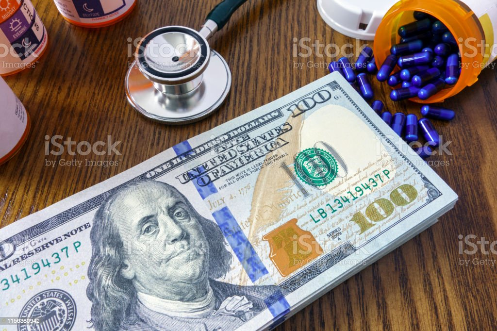 Medicine pills and pile of 100 dollar bills on wooden background
