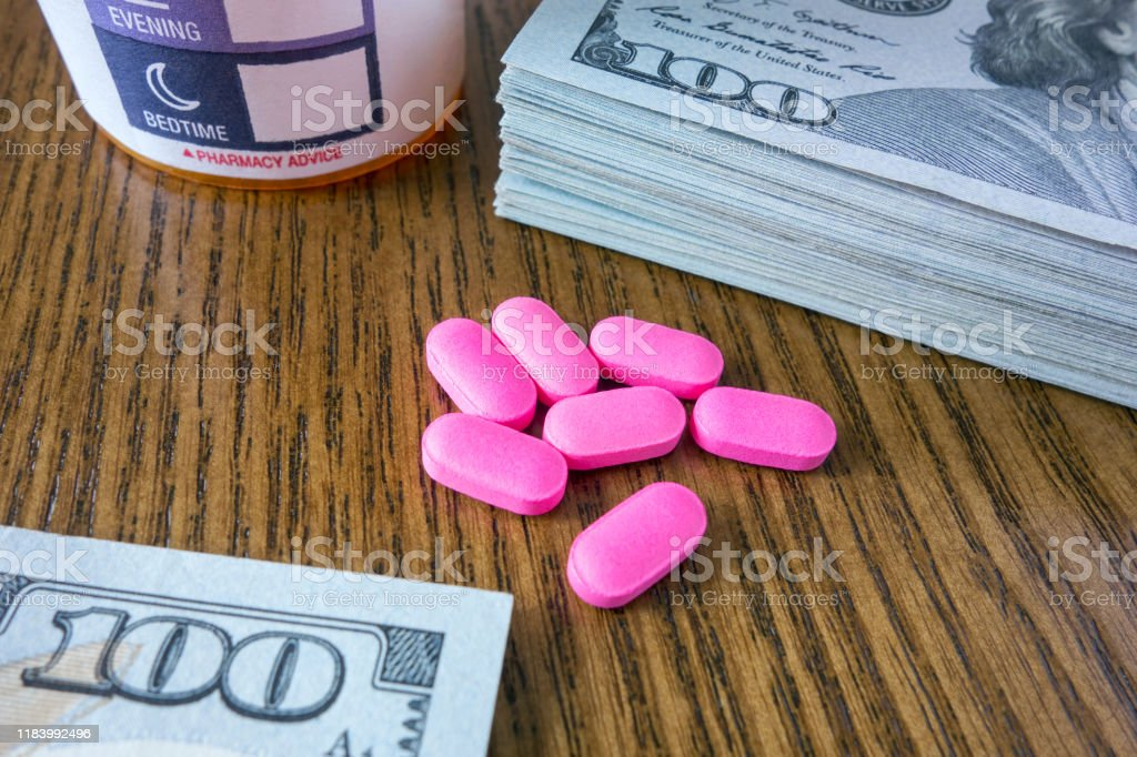 Medicine pills on a pile of 100 dollar bills and social security card