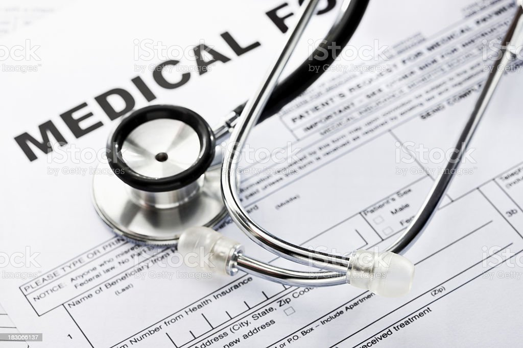 A stethoscope rests atop a blank medical form. Horizontal shot.