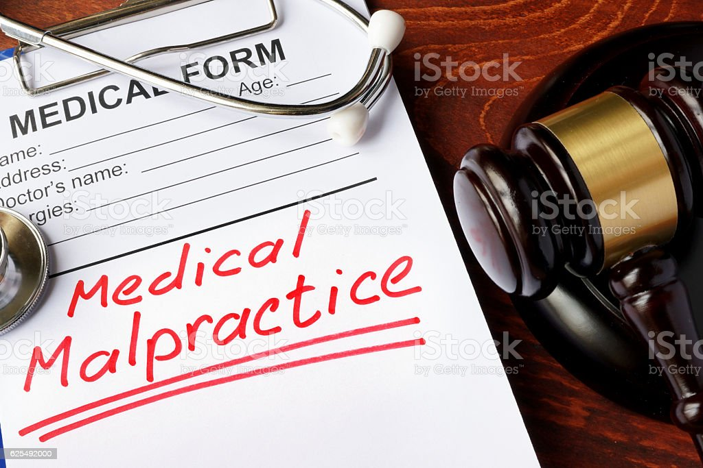 Medical form with words Medical Malpractice and gavel. – Foto