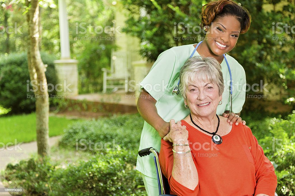 Medical:  Happy caregiver and patient outside a home. stock photo
