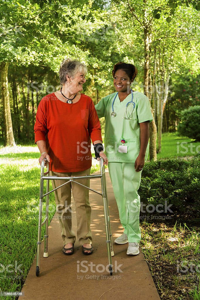 Medical:  Happy caregiver and patient taking a walk together. royalty-free stock photo