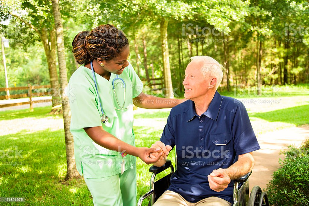 Medical:  Happy Caregiver visiting with senior man in wheelchair. royalty-free stock photo