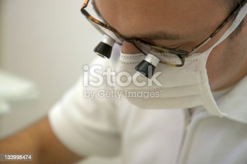 dentist wears a surgical mask and looks through his magnifying glasses