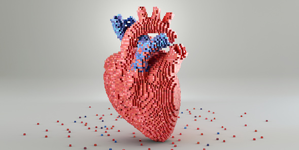 A conceptual image of a 3D model of a heart made from small multi-toned red and blue blocks. The model rests on a plain white surface, surrounded by blocks scattered at its base. A plain background with copy space.
