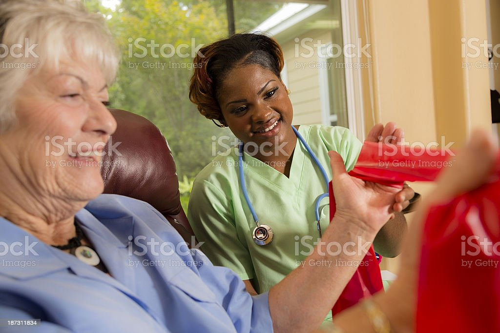 Senior woman does resistance band exercises with her physical...