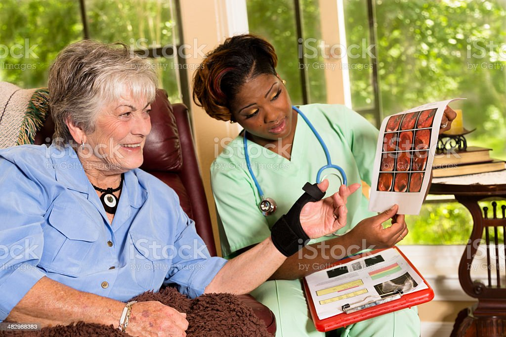 Medical:  Homehealth nurse showing colonoscopy report to senior woman. stock photo