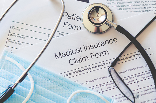 Medical Insurance claim form with stethoscope and surgical face mask. There are also other pieces of paperwork on the desk including a patient form