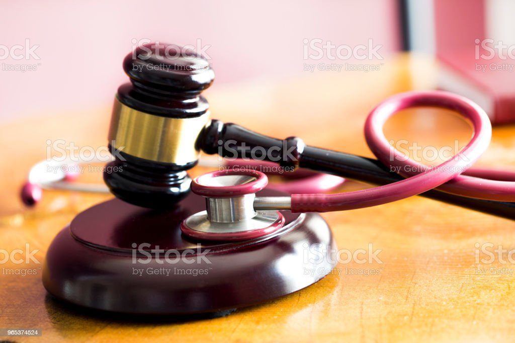 Medical law concept. Gavel and stethoscope on wooden table royalty-free stock photo
