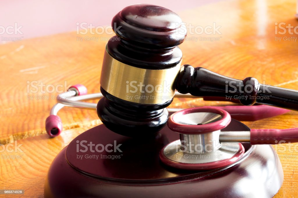 Medical law concept. Gavel and stethoscope on wooden table zbiór zdjęć royalty-free