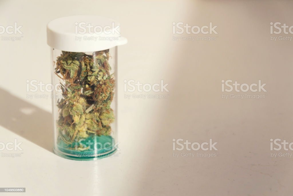 Medical marihuana, prescription cannabis in plastic bottle, close up isolated on white background stock photo