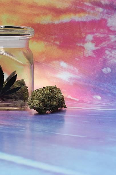 Medical marijuana in a jar with rainbow background image left stock photo