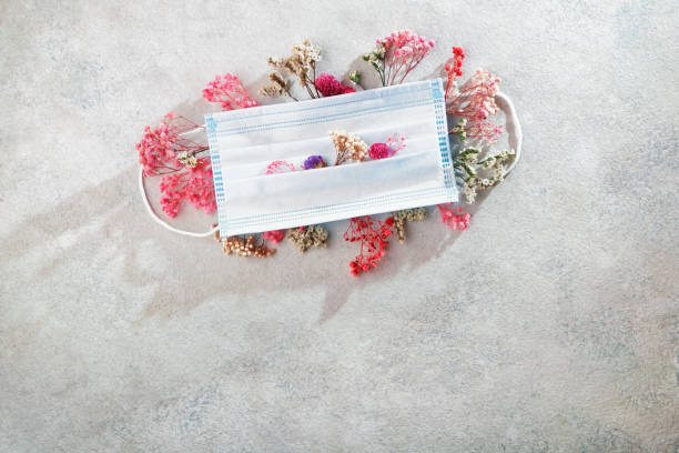 Medical mask and flowers. The concept of seasonal allergies, flu and spring quarantine stock photo