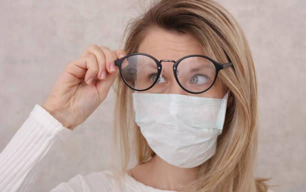 máscara médica e óculos embaçados. evite o toque facial, prevenção de coronavírus, proteção. - óculos - fotografias e filmes do acervo