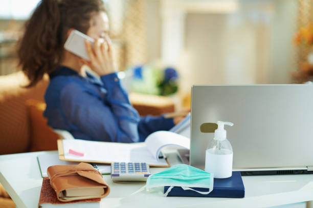 medical mask and hand disinfectant and woman talking on phone stock photo