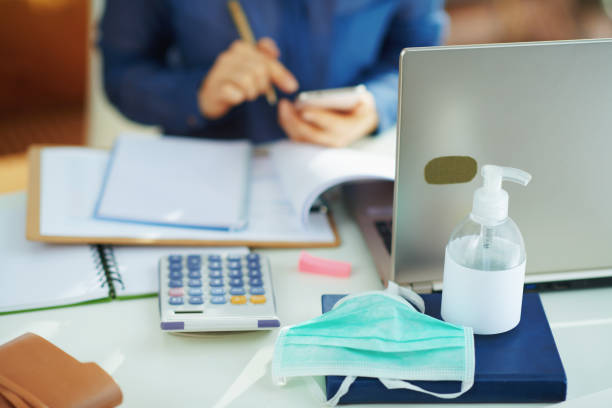 medical mask and hand disinfectant and woman working stock photo