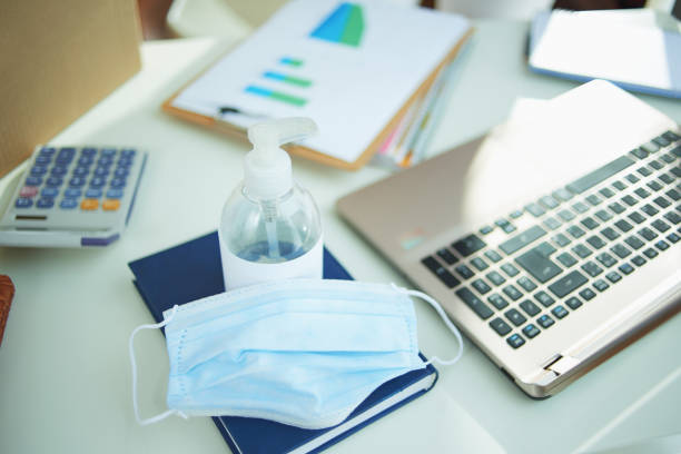medical mask and hand disinfectant on table in home office stock photo