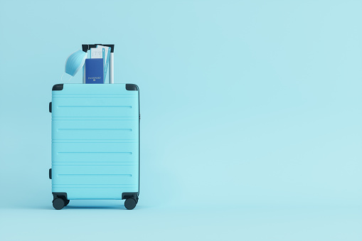 Medical Mask, Suitcase, Passport and Airplane Ticket on Blue Background