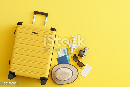 Medical Mask, Suitcase with Sun Hat, Camera, Passport, Airplane Ticket, Sunglasses and Airplane on Yellow Background