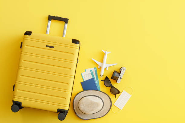 Medical Mask, Suitcase with Sun Hat, Camera, Passport, Airplane Ticket, Sunglasses and Airplane on Yellow Background Medical Mask, Suitcase with Sun Hat, Camera, Passport, Airplane Ticket, Sunglasses and Airplane on Yellow Background travel stock pictures, royalty-free photos & images