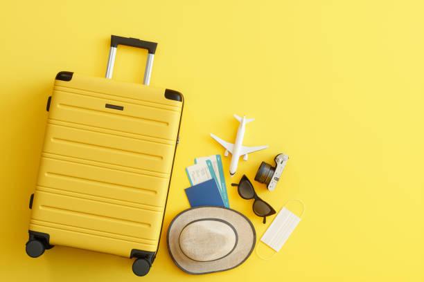 medicinsk mask, resväska med solhatt, kamera, pass, flygbiljett, solglasögon och flygplan på gul bakgrund - resande bildbanksfoton och bilder