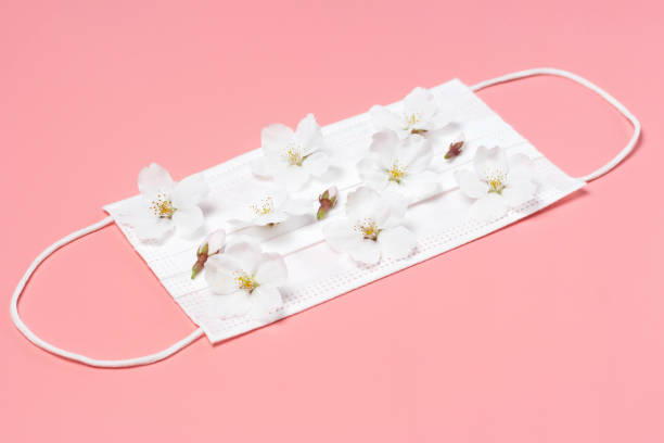 Medical mask with little white flowers on pink background. stock photo