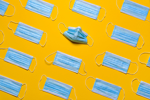 Flat lay with blue medical masks isolated on a yellow-colored background. Protective masks symmetrically arranged on a yellow paper.
