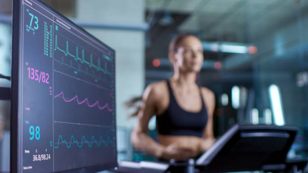 Medical Monitor Shows EKG Reading of a Woman Athlete Running on a Treadmill. Focus on Monitor. stock photo