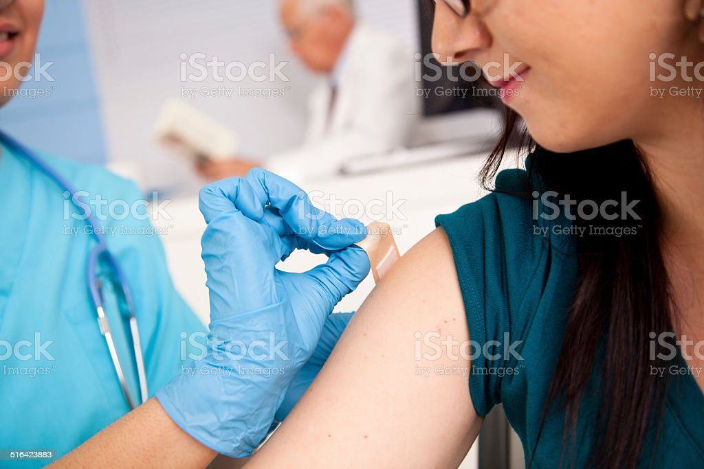 Medical: Nurse at pharmacy clinic giving flu shot to patient. stock photo