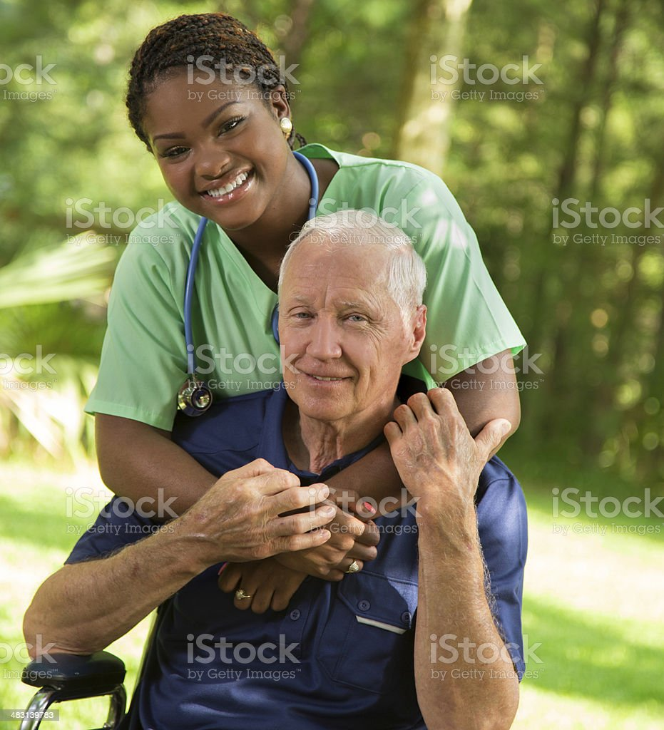 Medical:  Nurse giving senior wheelchair patient a hug. stock photo