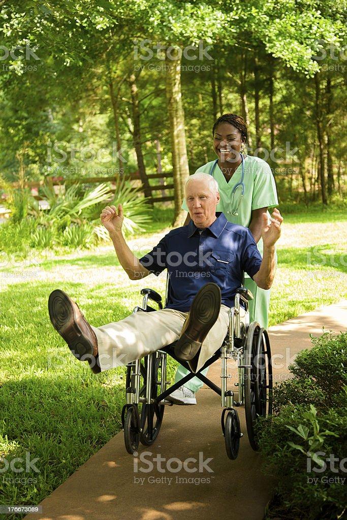 Medical:  Nurse giving wheelchair patient a fun ride. royalty-free stock photo