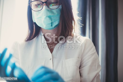 Medical nurse putting on blue sterilized surgical gloves