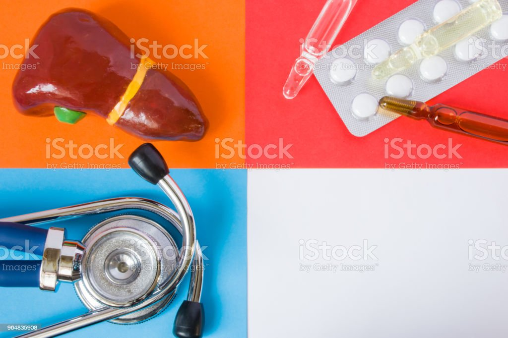 Medical or health care design concept photo-organ (liver), diagnostic medical tool (stethoscope) and medications (pills and vials) on blue, orange, red backgrounds with pure white space for text royalty-free stock photo