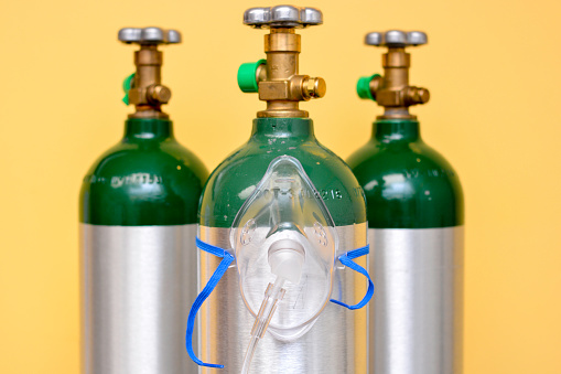 3 medical oxygen tanks on yellow background with oxygen mask on the center cylinder.