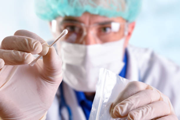 Medical person taking an oral sample with a cotton swab stock photo