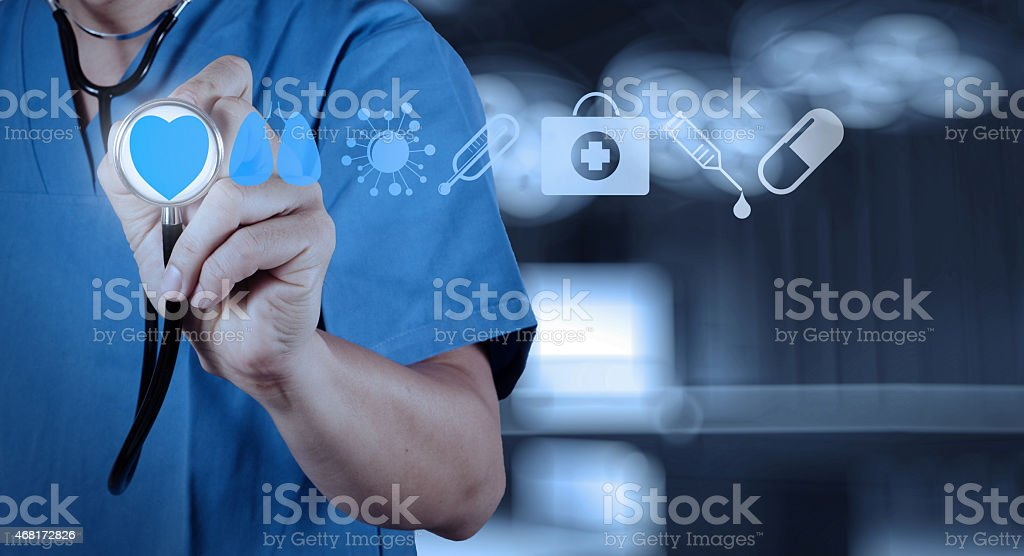 A medical physician holding a stethoscope up to a heart icon stock photo