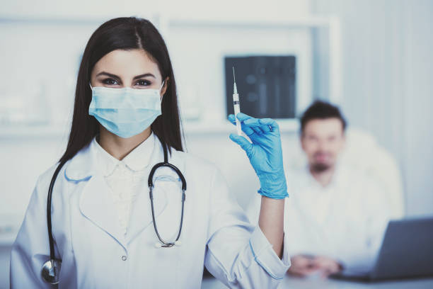 Medical Assistant doctor with a syringe. Against the background of the doctor sits at the table. tetanus stock pictures, royalty-free photos & images