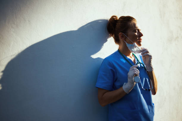 medical practitioner woman breathing outdoors in city near wall