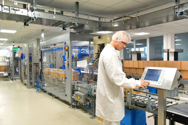 medical products manufacturing in a modern factory - worker operates modern industrial plant stock photo