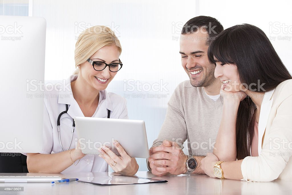 Medical professional and young couple smiling at tablet stock photo