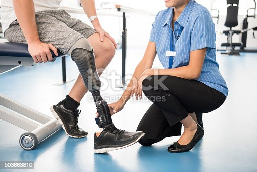 Male amputee with prosthesis in hospital. Man sitting on chair with nurse touching prosthetic limb. Female nurse working with male patient. Rehabilitation, recovery, improvement.